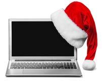 Bärbar dator- och Santa Claus hatt som isoleras på vit Fotografering för Bildbyråer