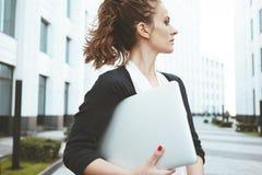 Bärbar dator och ställning för nätt håll för affärskvinna modern bland stads- utrymme royaltyfri bild