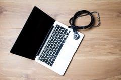 Bärbar dator- och stetoskopöverkant arkivfoton