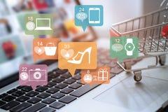 Bärbar dator och vagn med symbolsonline-shopping och det sociala nätverket Arkivbilder
