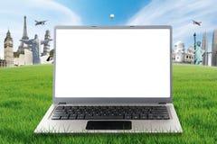 Bärbar dator på gräs med världsmonumenten Arkivfoto