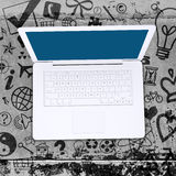 Bärbar dator på konkret golv med olika sociala symboler Royaltyfria Bilder