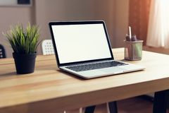 Bärbar dator på tabellen i kontorsrumbakgrunden, för montage för diagramskärm royaltyfri bild