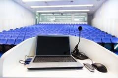 Bärbar dator på talarstolen i konferenskorridor Arkivfoto