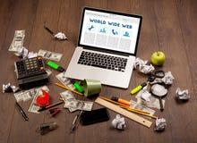 Bärbar dator på träskrivbordet med kontorssuplies Fotografering för Bildbyråer