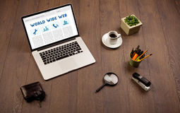 Bärbar dator på träskrivbordet med kontorssuplies Arkivbilder