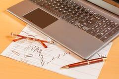 Bärbar dator, penna och exponeringsglas på kontorsskrivbordet Selektiv fokus på exponeringsglas Fotografering för Bildbyråer