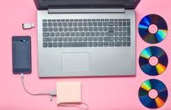 Bärbar dator smartphone, maktbank, CD drev, USB exponeringsdrev på en rosa bakgrund Modernt och omodernt digitalt massmedia och g arkivfoto