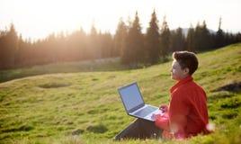 bärbar dator som använder utomhus kvinnabarn Arkivfoto