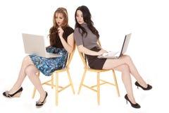 bärbar dator som kikar två kvinnor Arkivbilder