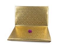 Bärbar dator som slås in i guld- gåvapapper som isoleras på vit Arkivbild