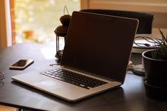 Bärbar dator, växt och smartphone med ljus från fönster royaltyfri foto