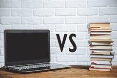 Bärbar dator vs bunt av böcker books isolerat gammalt för begrepp utbildning arkivfoto