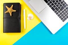 Bärbar datordator, loppanteckningsbok och snäckskal och sjöstjärna över blått och gulingbakgrund Arkivbilder