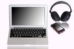 Bärbar datordator med hörlurar med mikrofon och mobiltelefonen Royaltyfri Foto
