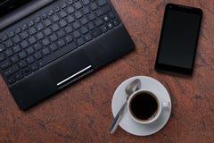 Bärbar datordator med smartphonen och koppen kaffe på granityttersida arkivbilder