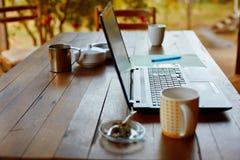 Bärbar datordator och kaffe i trädgården royaltyfria foton