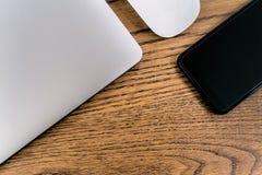 Bärbar datordator och smartphone, mus på tabellen watch för penna för begreppsanteckningsbokkontor arkivfoton