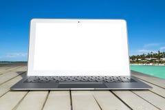 Bärbar datordator på trätabellen Bästa havsikt tropisk bakgrundsö Öppna tomt tomt utrymme för bärbar datordatoren Bekläda beskåda Arkivbild