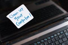 Bärbar datordatoren på trätabellen med anmärkningen GÖR REN UPP DIN DATOR Arkivbild