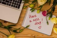 Bärbar datordatoren, text har en trevlig dag, och eustomaen blommar uppvaktar på royaltyfri fotografi