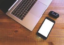 Bärbar datormellanrumsmobil och hörlurar på träbakgrund Förlöjliga upp med den tomma smartphoneskärmen och twshörlurar med mikrof fotografering för bildbyråer