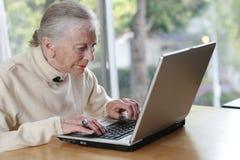 bärbar datorpensionärkvinna Fotografering för Bildbyråer