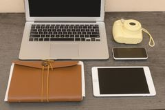 Bärbar datortangentbord, gul kamera, anteckningsbok, minnestavla och smartphone arkivbilder