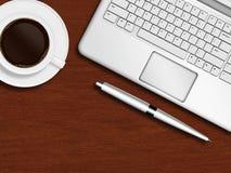 Bärbar datortangentbord, penna och kopp kaffe på träskrivbordet Fotografering för Bildbyråer