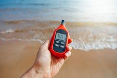 Bärbar termometer i handen som mäter utomhus- lufttemperatur och fuktighet royaltyfri bild