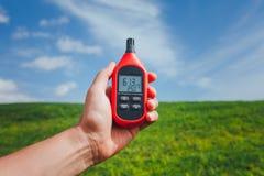 Bärbar termometer i handen som mäter utomhus- lufttemperatur och fuktighet fotografering för bildbyråer
