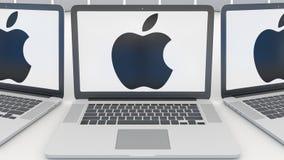 Bärbara datorer med Apple Inc logo på skärmen modernt kontor för byggnadsingång Begreppsmässig ledare 3D för datateknik royaltyfri illustrationer