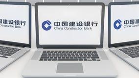 Bärbara datorer med den China Construction Bank logoen på skärmen Tolkning för ledare 3D för datateknik begreppsmässig Royaltyfri Bild
