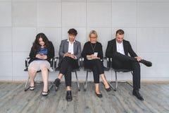 Bärbara datorer och smartphones för multietniska arbetssökanden som sitter upptagna användande förbereder sig för att rekrytera s arkivfoton