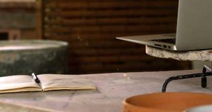 Bärbara datorn den öppnade boken, lergods bowlar på en worktop arkivfilmer