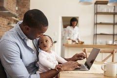 Bärbara datorn för faderAnd Baby Daughter bruk som moder förbereder mål Arkivbilder