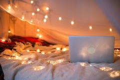 Bärbara datorn ligger på sängen i bakgrunden av ett julgranljus, slät rörelse Arkivfoto