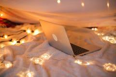 Bärbara datorn ligger på sängen i bakgrunden av ett julgranljus, slät rörelse Royaltyfria Bilder