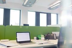 Bärbara datorn med spiralböcker och landlinen ringer på skrivbordet på kontoret Royaltyfri Foto