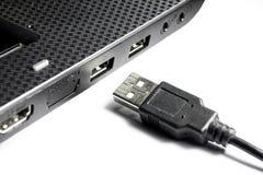 Bärbara datorn med USB kontaktdon och USB kablar på en vit bakgrund Arkivfoto