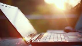 Bärbara datorn och musen det fria på solnedgången med den härliga linssignalljuset verkställer 1920x1080 stock video