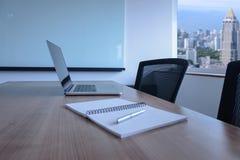 Bärbara datorn och pennan på notepaden för dagordning höll på tabellen i tomt företags konferensrum med cityscapesikt på bakgrund arkivbild