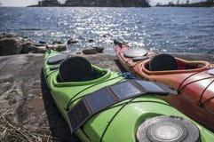 Bärbara solpaneler ligger på en kajak vid sjön och ackumulerar arkivbilder