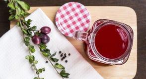 Bärfruktsaft i exponeringsglas på den lekmanna- skärbrädalägenheten Royaltyfri Foto