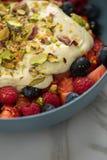 Bärfruktsallad med jordgubbar, blåbär, hallonet, pistaschen, citronpiff och linoljakvarkkräm i den blåa bunken för fotografering för bildbyråer