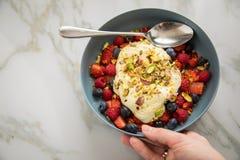 Bärfruktsallad med jordgubbar, blåbär, hallonet, pistaschen, citronpiff och linoljakvarkkräm i den blåa bunken för arkivfoto