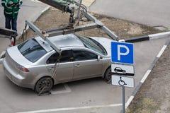 Bärgningsbilen laddar bilen för kränkningen av parkeringsreglerna fix arkivfoto
