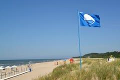 BÄRNSTEN RYSSLAND Det internationella tecknet av den blåa flaggan för stränder fladdrar över stadsstranden, den Kaliningrad regio arkivbilder