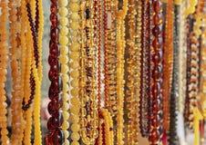 Bärnstensfärgad bakgrund av pärlor Bärnstensfärgade pärlor i smycken shoppar fönstret Smyckendesign arkivbild