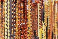Bärnstensfärgad bakgrund av pärlor Bärnstensfärgade pärlor i smycken shoppar fönstret Smyckendesign arkivfoto